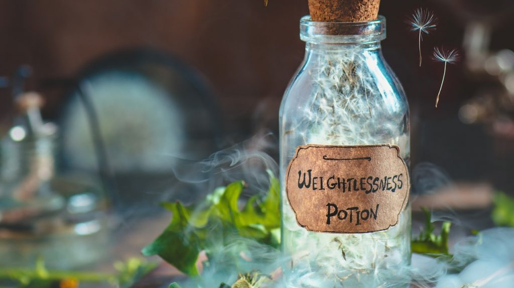 Glass potion bottle with dandelion seeds and handcrafted label in a magical still life with smoke