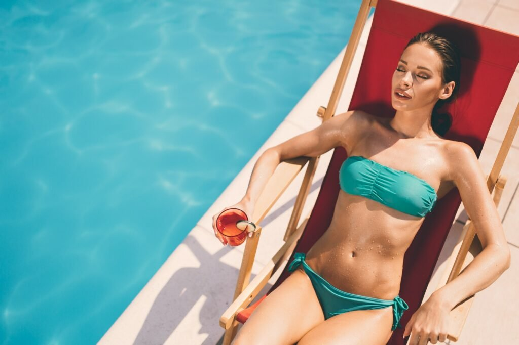 Woman sun tanning by the swimming pool