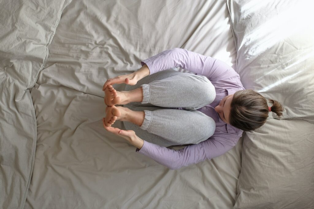 Woman doing Knee to Chest Pose on Bed