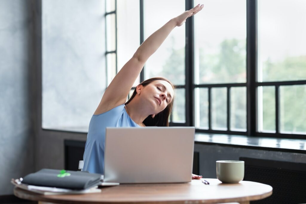 woman performing a side stretching exercise for the spine working at home.