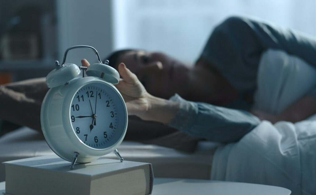Woman waking up in the morning and dreading the alarm clock