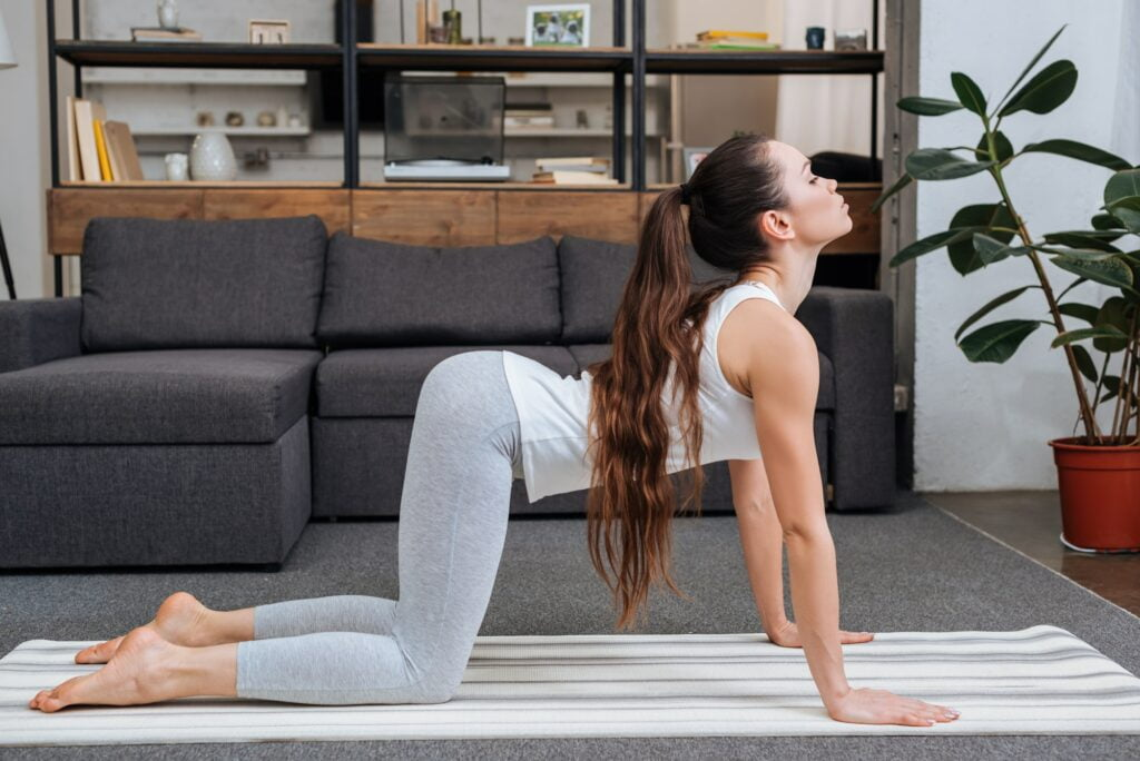 young woman practicing cat pose at home in living room